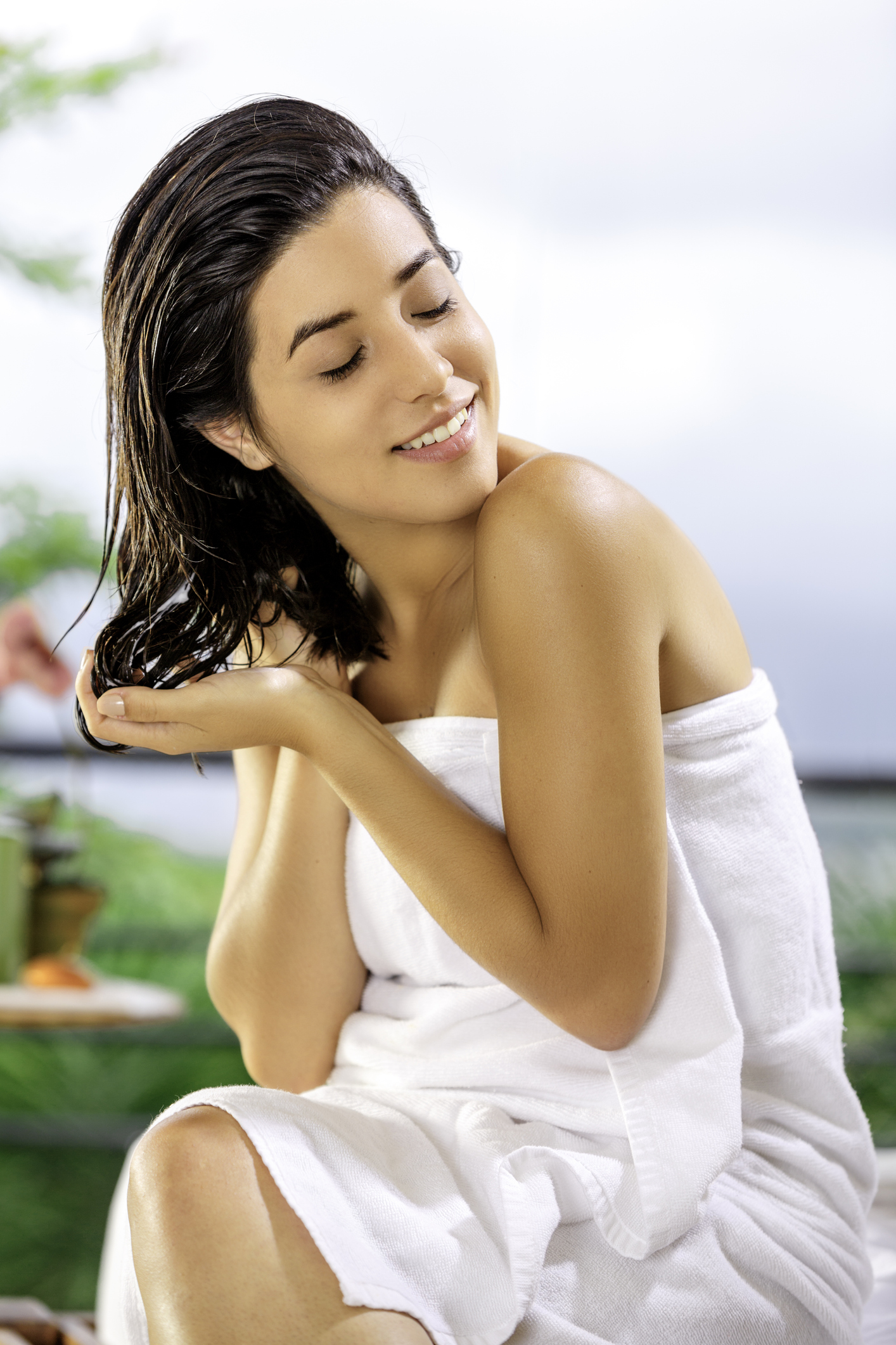 Cute and happy Hispanic young woman doing self hair treatment after bath